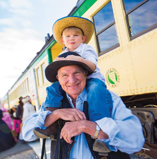 Young Boy Sits on Grandfather Shoulders in Front of Train