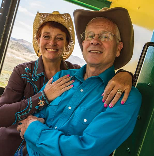 Couple in Cowboy Hats Standing in a Train